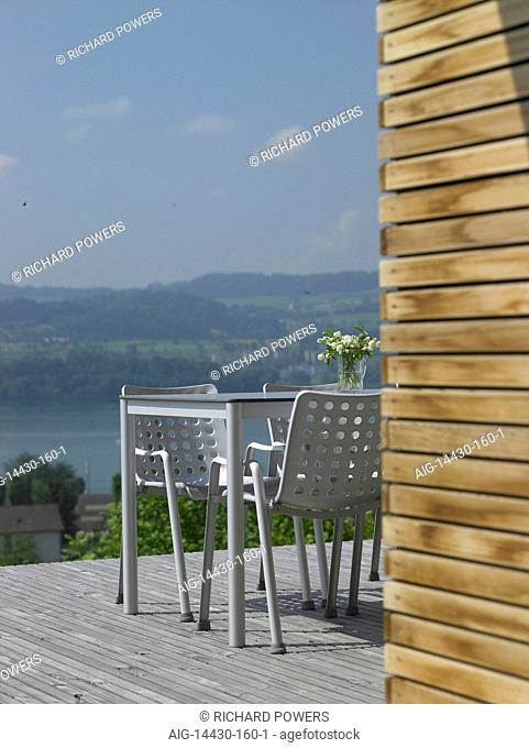 Table and chairs on decked terrace overlooking countryside with river below, Switzerland