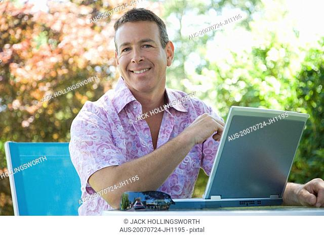 Portrait of a mature man sitting in front of a laptop and smiling