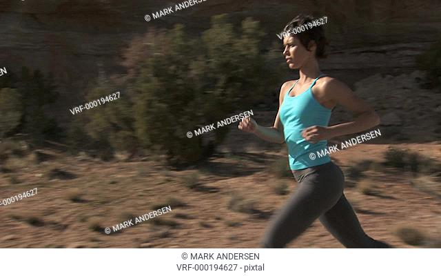 Woman running outdoors with red rock