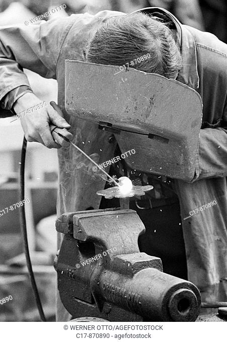 Seventies, black and white photo, handicraft, street party, funfair, Flachs Market in Krefeld, metalsmith forging with protective mask, welding work, D-Krefeld