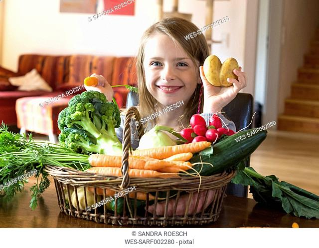 Portrait of grinning girl with wickerbasket of fresh vegetables at home