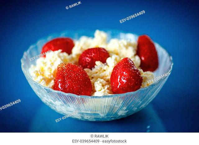 cottage cheese with strawberries in a plate on a blue background
