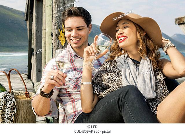 Young couple drinking wine on old pier, Cape Town, Western Cape, South Africa