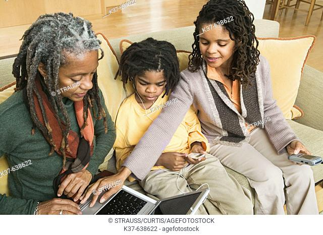 3 generations of African American family at home, with grandma using laptop being advised by older daughter & her grandson listening to his ipod
