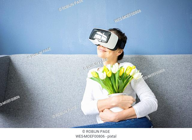 Smiling woman sitting on couch wearing VR glasses holding bunch of tulips