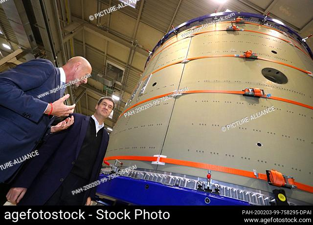 03 February 2020, Bavaria, Augsburg: Markus Söder (CSU, r), Bavarian Minister President, standing in front of a part of the Ariane 6 rocket together with Hans...
