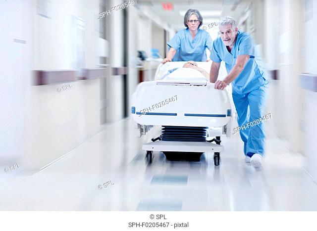 Two doctors pushing hospital bed