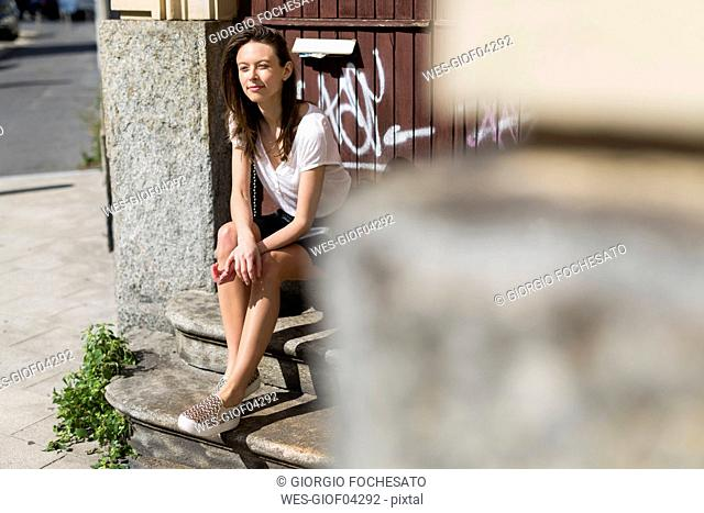 Smiling young woman sitting on stairs in the city