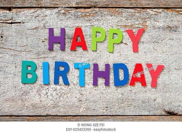 "The colorful words """"HAPPY BIRTHDAY"""" made with wooden letters on old wooden board"