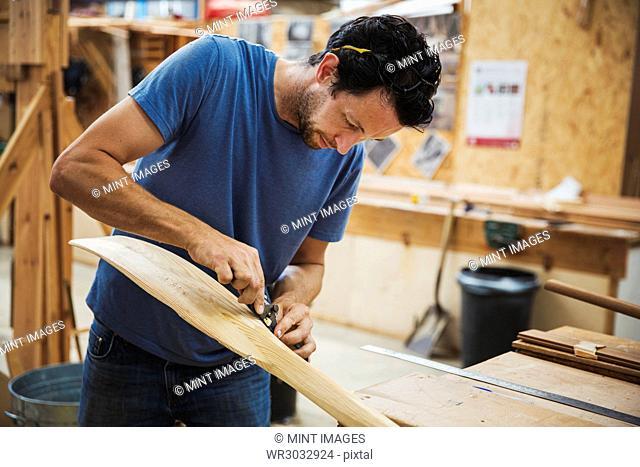 Man standing in a boat-builder's workshop, working on a wooden oar
