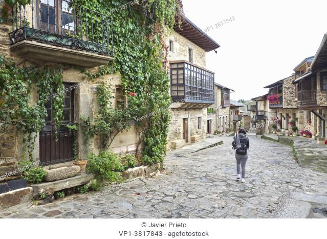 A woman with her back turned walk through the streets of the historic center of Puebla de Sanabria. Zamora. Castile and Leon. Spain