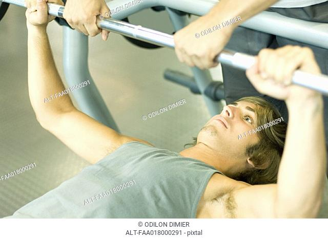 Man lifting barbell while second man spots