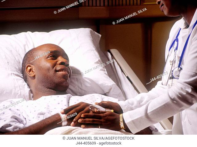 Black man patient in bed with nurse holding hand