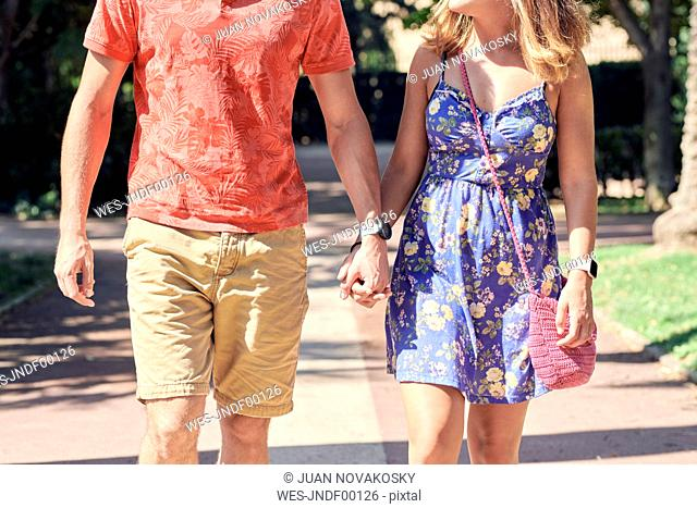 Young couple walking hand in hand through a park