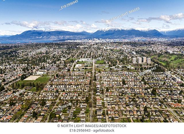 Canada, BC, Richmond, Vancouver. Aerial view of the city of Richmond, a suburb of Vancouver. Vancouver city center visible in the distance