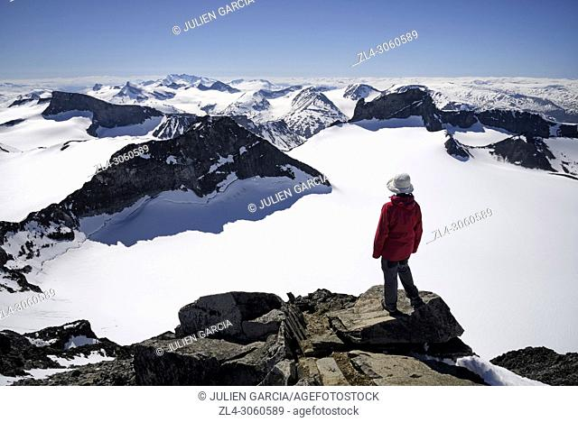 Norway, Oppland, Vaga, Jotunheimen National Park, trekker at the summit of Galdhopiggen, the tallest mountain in Norway and Scandinavia at 2469m, Model Released