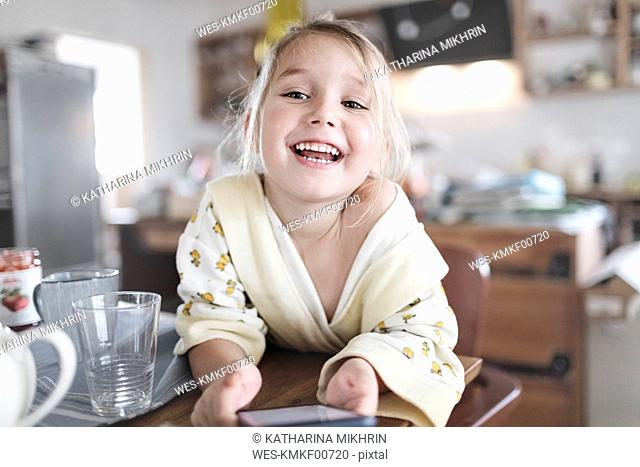 Portrait of happy little girl with smartphone in the kitchen