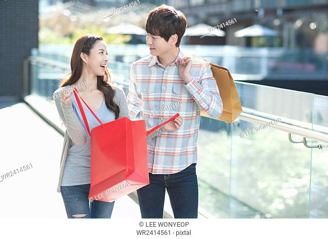 Young smiling couple having a date with shopping bags