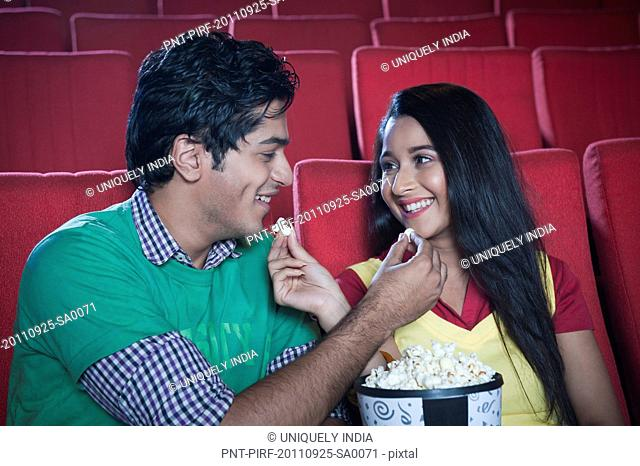 Couple feeding popcorn to each other and smiling in a cinema hall