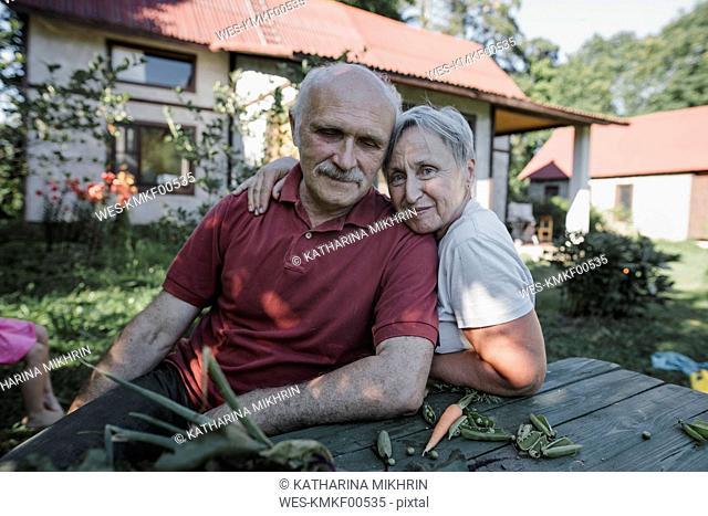 Portrait of senior couple sitting at garden table