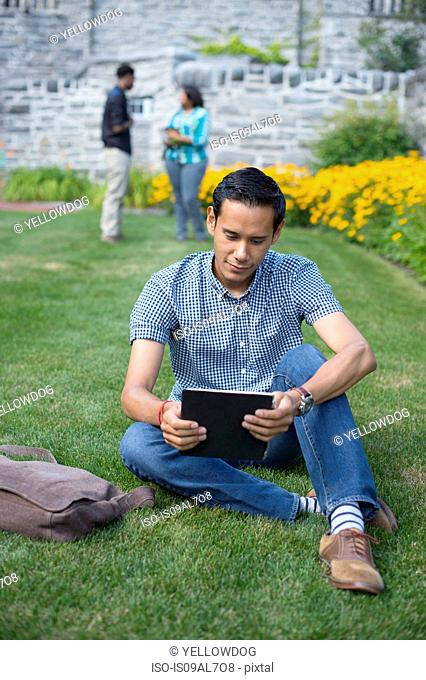 Male student sitting on grass using digital tablet