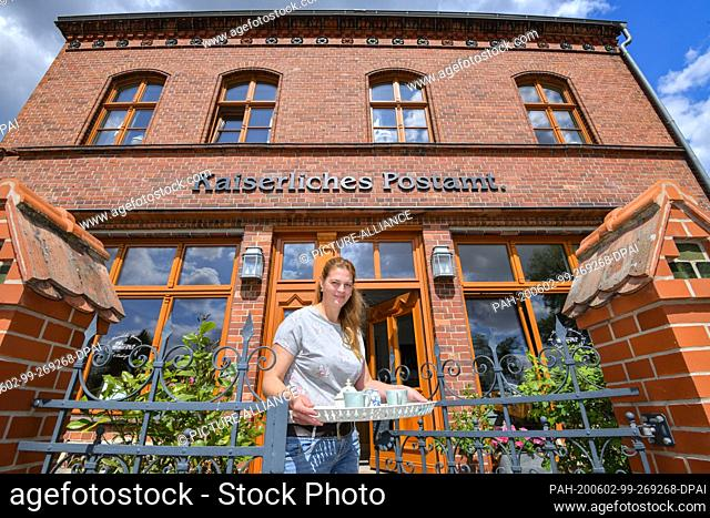 27 May 2020, Brandenburg, Biesenthal: Pamela John, operator of the Imperial Post Office, stands in front of her building with a coffee tray