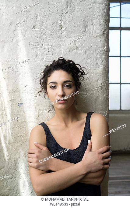Serious young woman arms folded staring