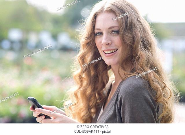 Portrait of young woman texting on smartphone in garden