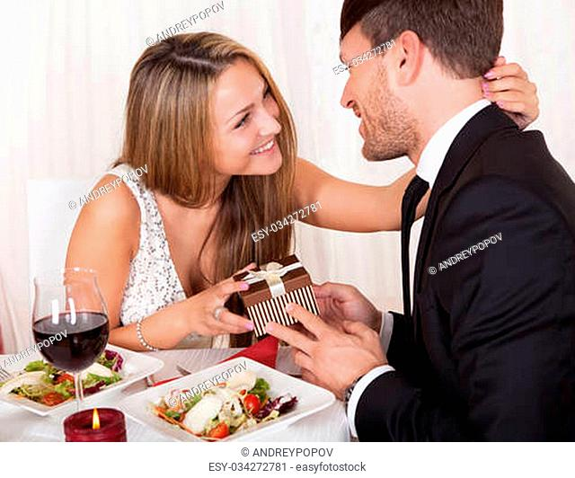 Happy young woman gives a gift to her partner. Romantic dinner setting with young couple dressed in evening wear