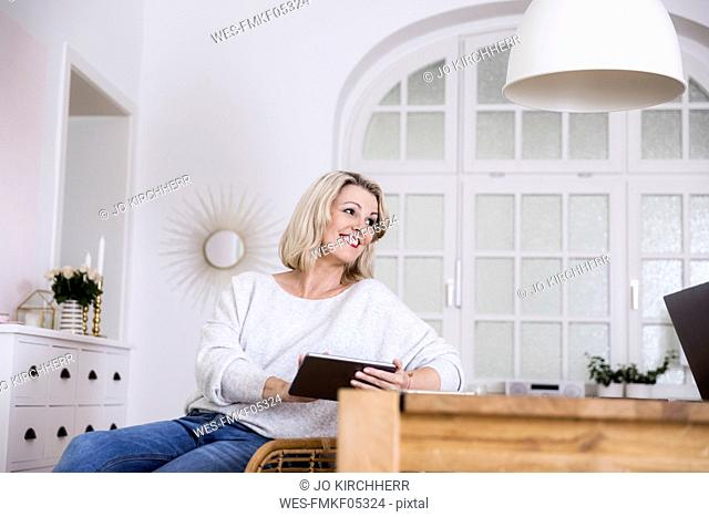 Portrait of smiling blond mature woman using digital tablet at home