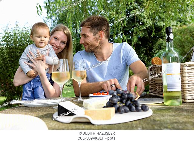 Mid adult couple and baby daughter sitting at picnic table in garden