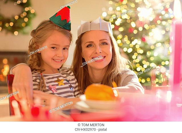 Portrait smiling mother and daughter wearing elf hat and paper crown at Christmas dinner table