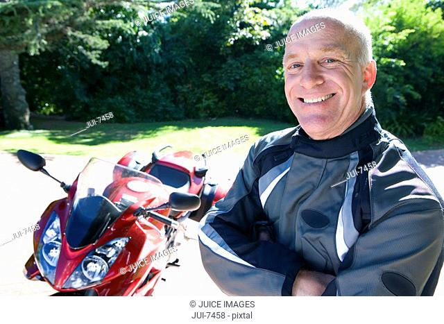 Senior man, in leather jacket, standing beside red motorbike on driveway, smiling, side view, portrait
