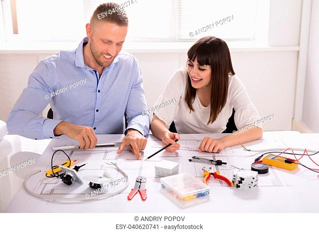 Smiling Young Male And Female Architect Working On Blueprint In Office