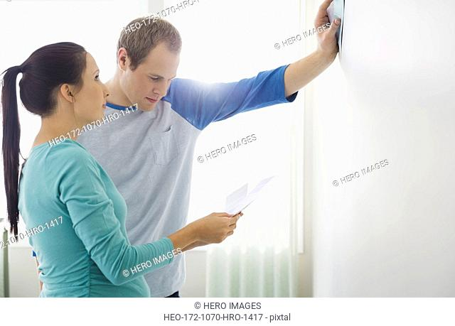 Young couple holding color swatches against bare wall