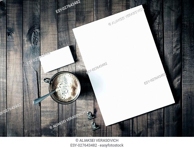 Photo of blank stationery set on vintage wooden table background. Letterhead, coffee cup and business cards. Branding template