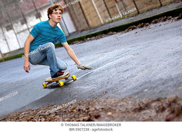 Teenager riding a longboard downhill on a wet street