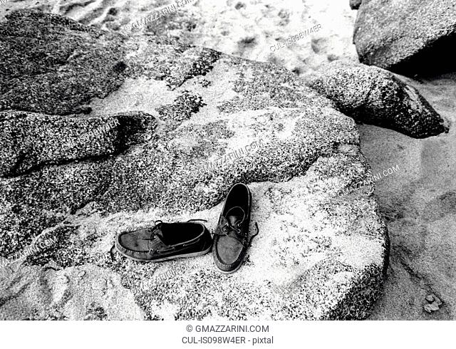 Pair of shoes on rocks on beach