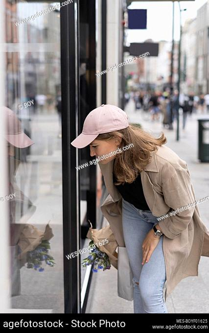Young woman looking at glass door while standing on footpath