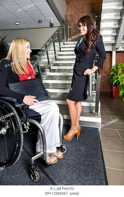 Two professional business women in the lobby of an office, one of which is a paraplegic in a wheelchair; St. Albert, Alberta, Canada