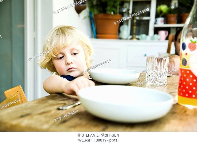 Portrait of blond little boy laying the table