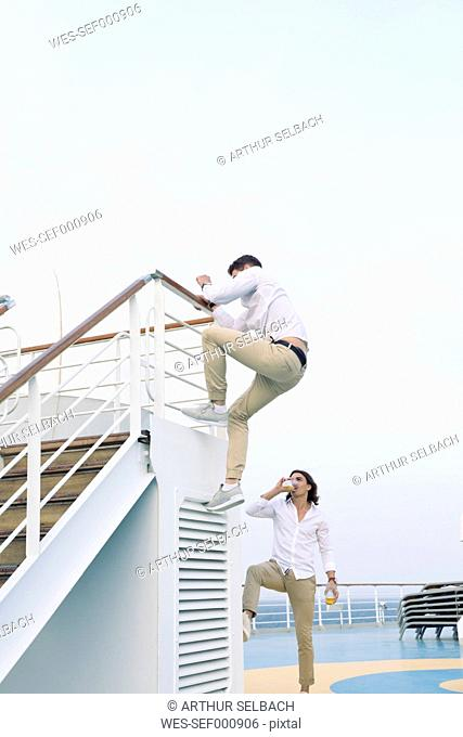 Two young men messing about on cruise ship, climbing on railing