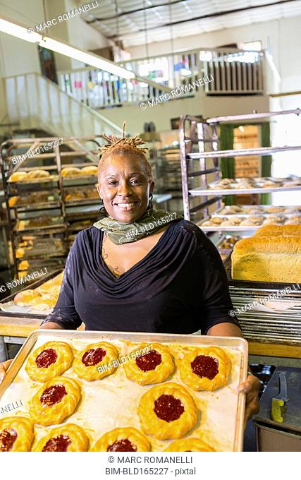 Black baker holding tray of pastries in bakery kitchen
