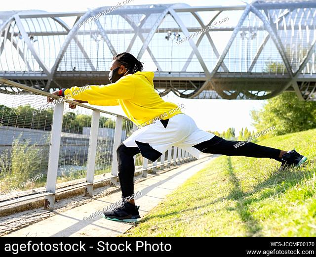 Male sportsman wearing face mask stretching while exercising against elevated walkway