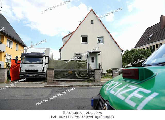 14 May 2018, Germany, Nuremberg:Police vehicles are parked outside the house of the partner of a mailwoman, who has been missing for the last four years