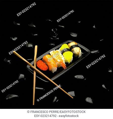 assorted sushi plate on black pebbles over black background