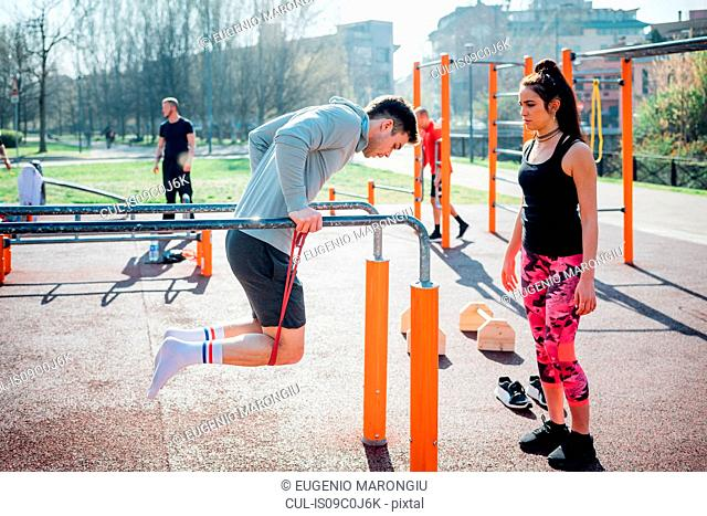 Calisthenics at outdoor gym, trainer watching young man on parallel bars
