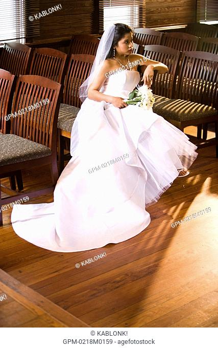 Young Asian bride in wedding dress sitting in wooden chairs of church holding bouquet, high angle view