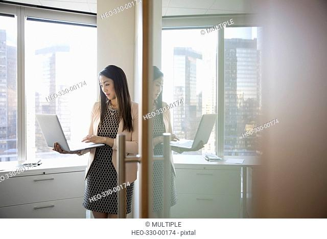 Businesswoman using laptop in highrise office