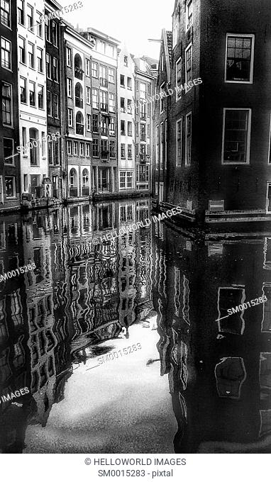 Black and white image of typical Dutch architecture reflected in narrow canal, Amsterdam, Netherlands